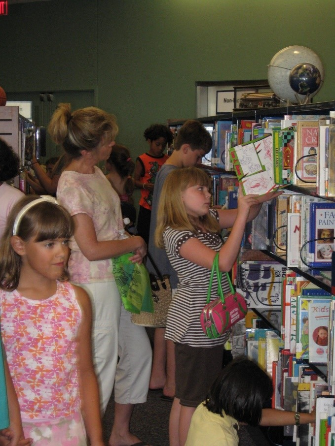 Crowded asiles while children select books in the youth area.